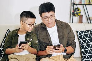 Vader en zoon samen op smartphone