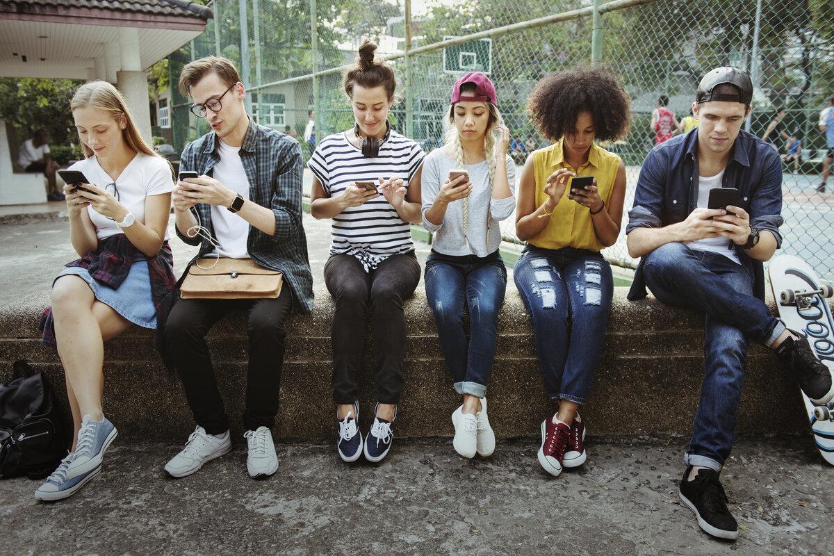 afbeelding van zes jongeren op hun smartphone bij artikel over fear of missing out