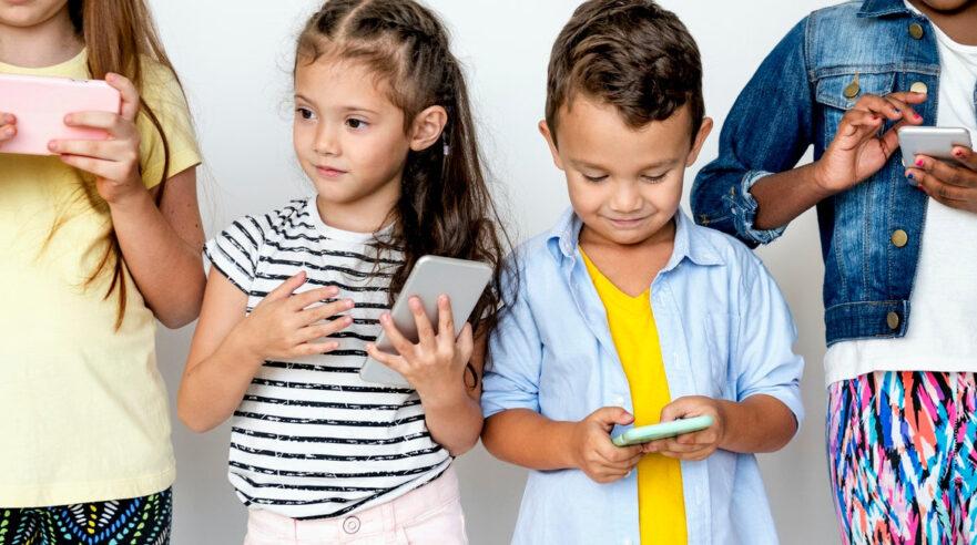 Jonge kinderen spelend met telefoons