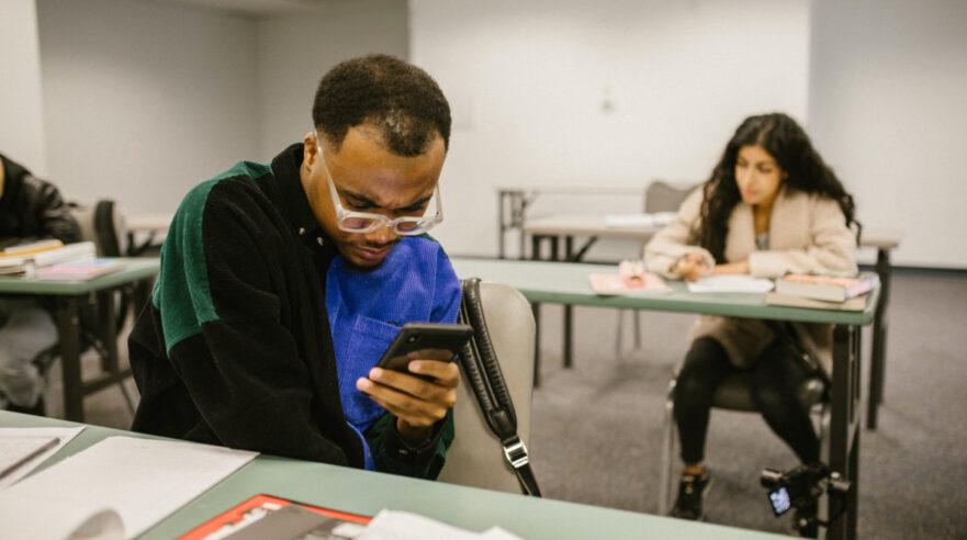 Jongeren in klaslokaal met smartphones