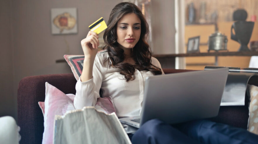 Jonge vrouw met bankpas en laptop in woonkamer