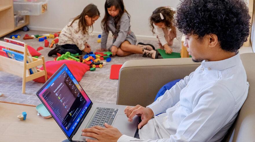 Kind met laptop, met spelende kinderen op de achtergrond