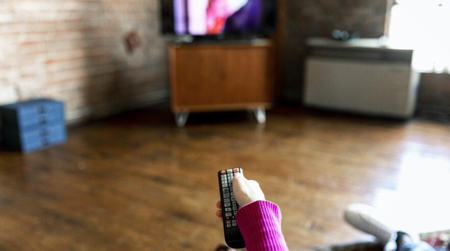 Persoon bedient televisie met afstandbediening