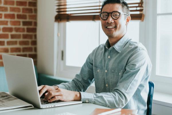 Man werkend op laptop aan bureau