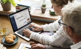 koppel achter laptop volgen online alliantie café
